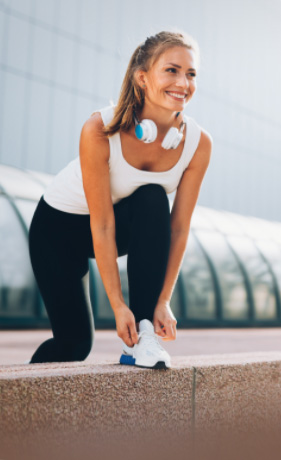 Woman wearing black and white workout clothes, tying her tennis shoe before a run