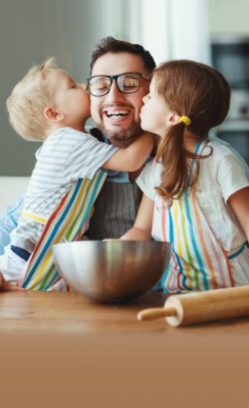 Man with glasses getting a kiss from his son and daughter while baking in the kitchen