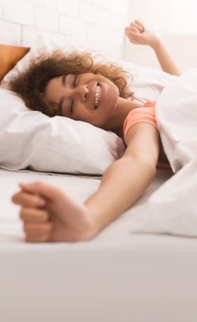 woman with curly brown hair, wearing an orange shirt, waking up and stretching in her bed