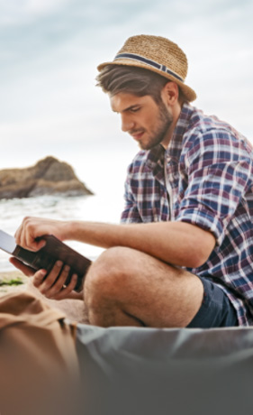 man in shorts, a plaid shirt and a straw hat, reading a book on the beach