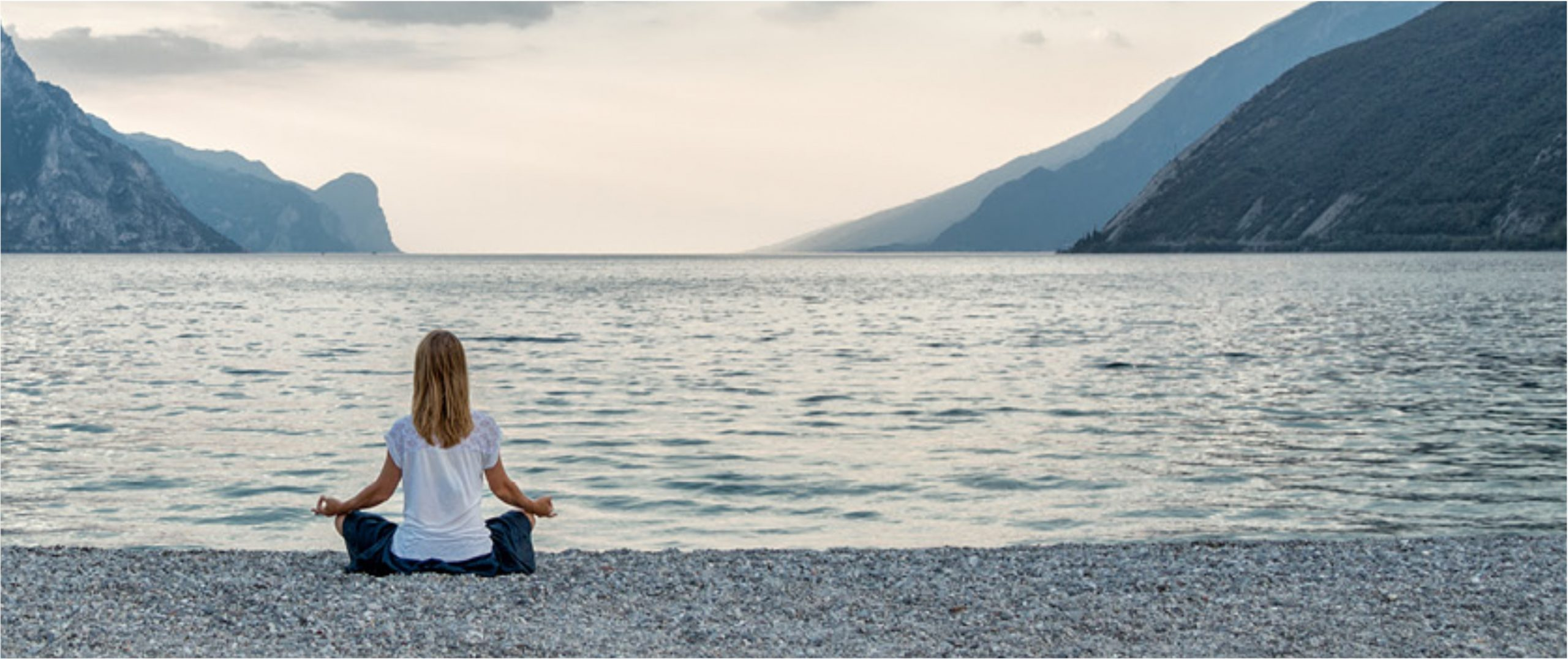 blonde haired woman, in a white shirt meditating on the edge of the water