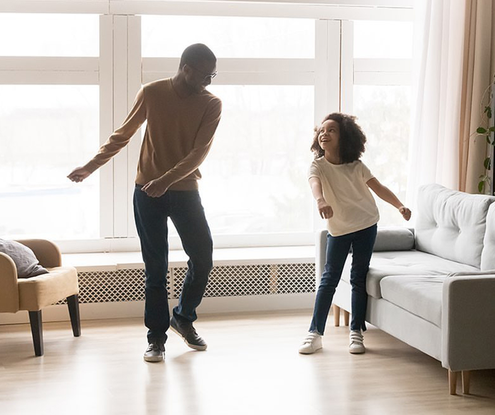 father and daughter dancing the floss in living room