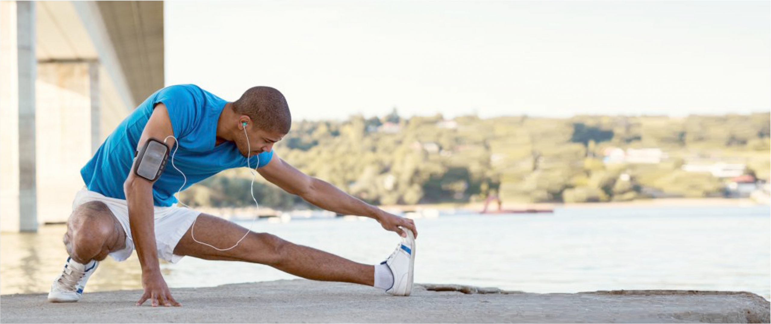 man, listening to his Iphone, performing a runners stretch in front of a lake