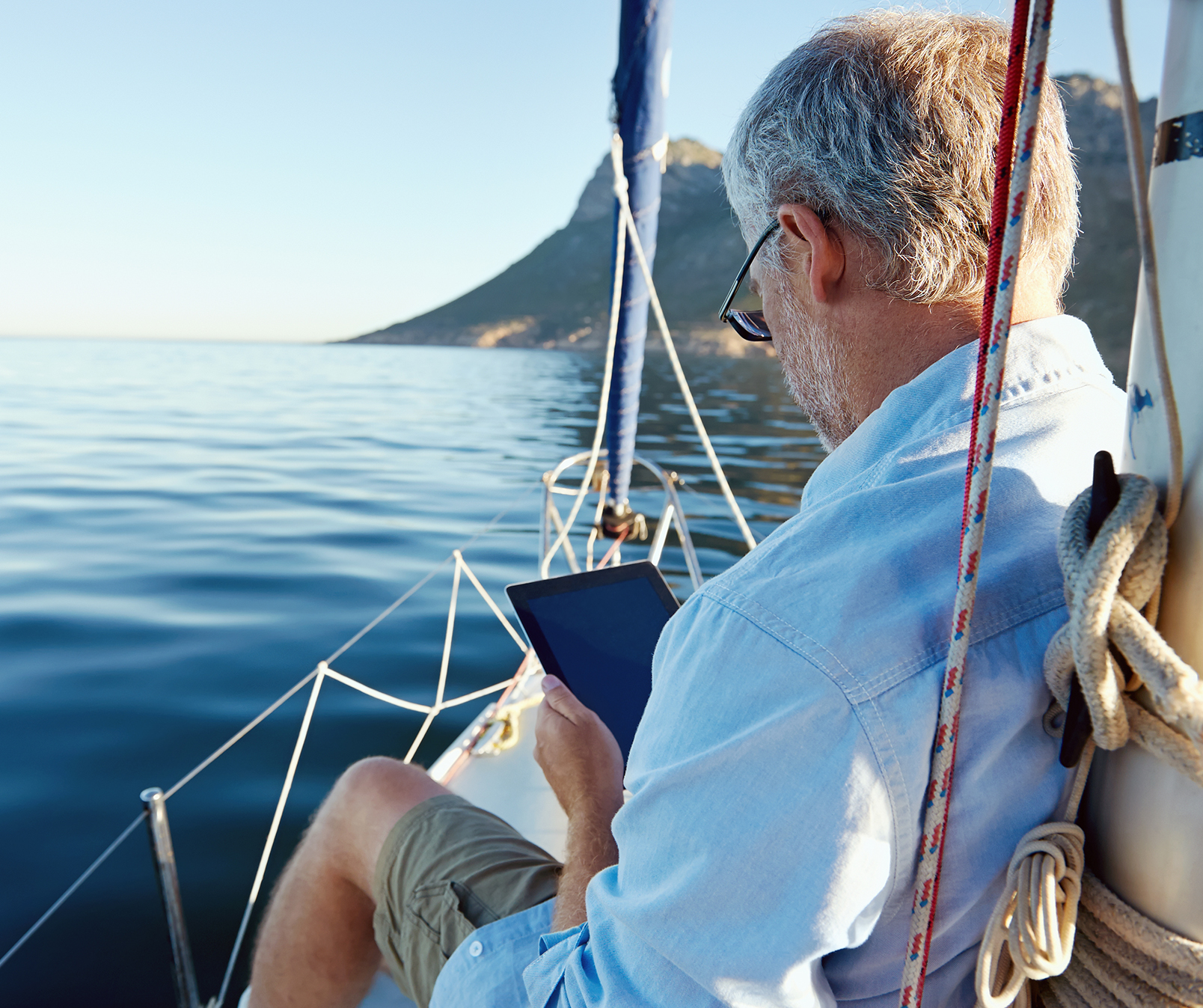 Elderly man, reading his iPad on a sailboat