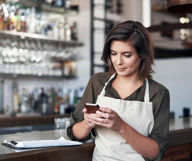 Female bartender with short brown hair looking at her cell phone