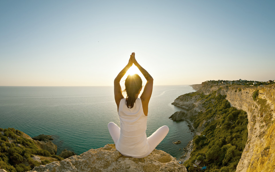 endocannabinoid system and CBD woman practicing yoga on a rock overlooking the ocean