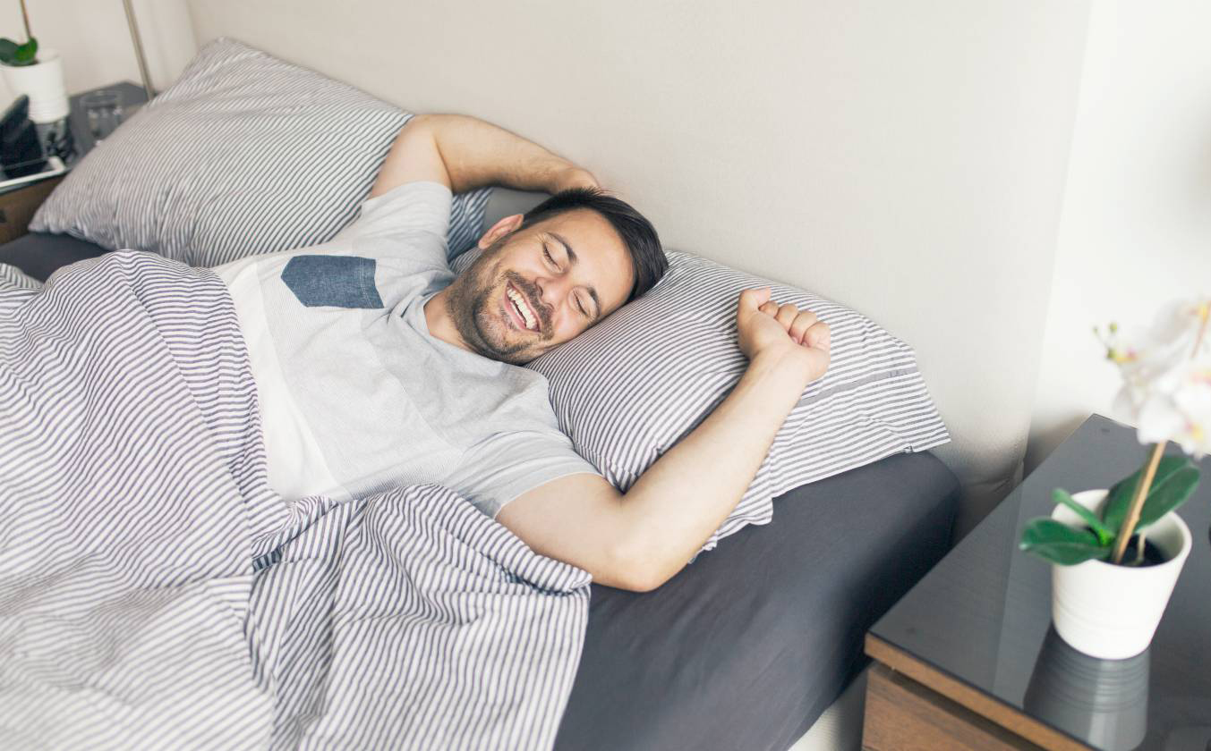 man resting in bed from taking melatonin and cbd for sleep quality