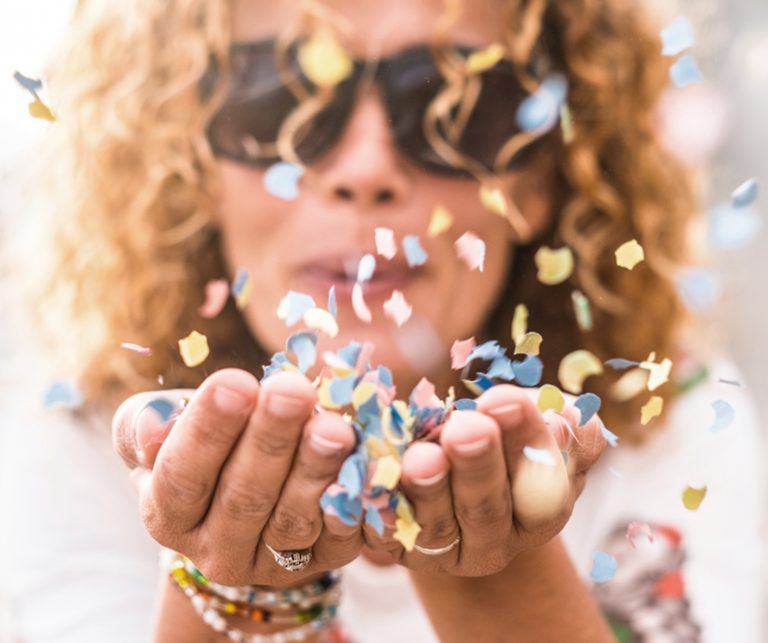 curly-haired woman in black sunglasses blowing confetti out of her hands