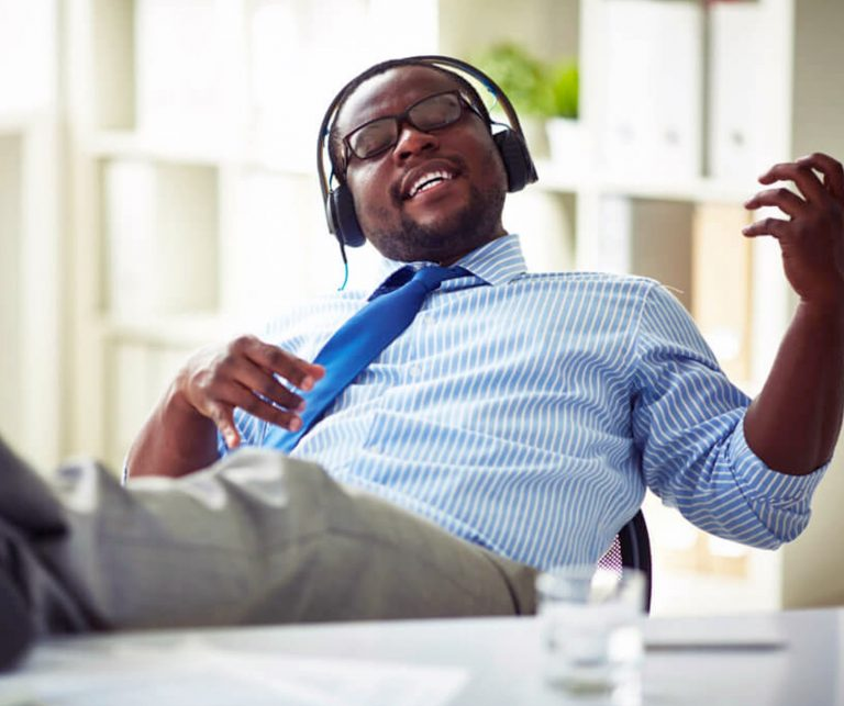 black man with headphones listening to music and playing air guitar at work