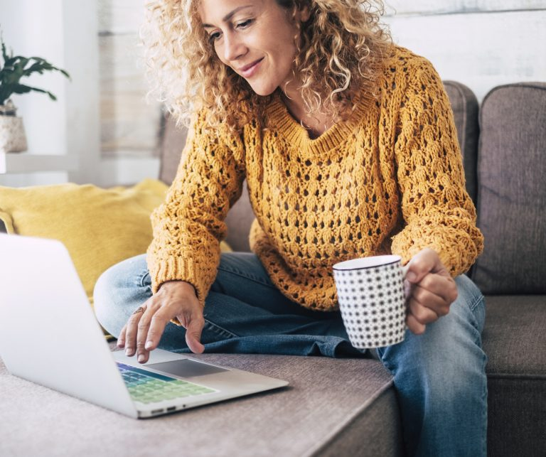 curly-haired blonde woman in a yellow sweater browsing her laptop on the sofa while drinking a cup of coffee