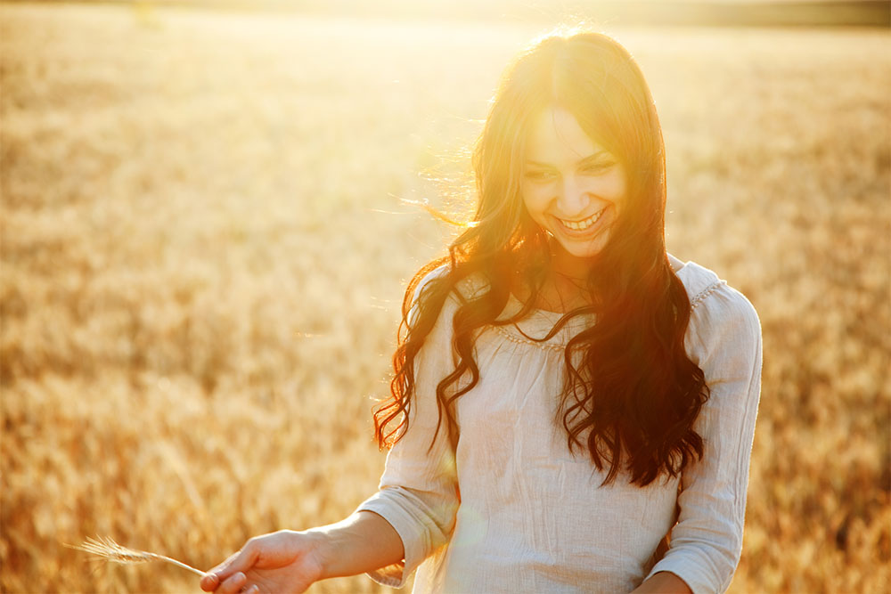 girl in wheat field happy after taking CBD and MCT oil