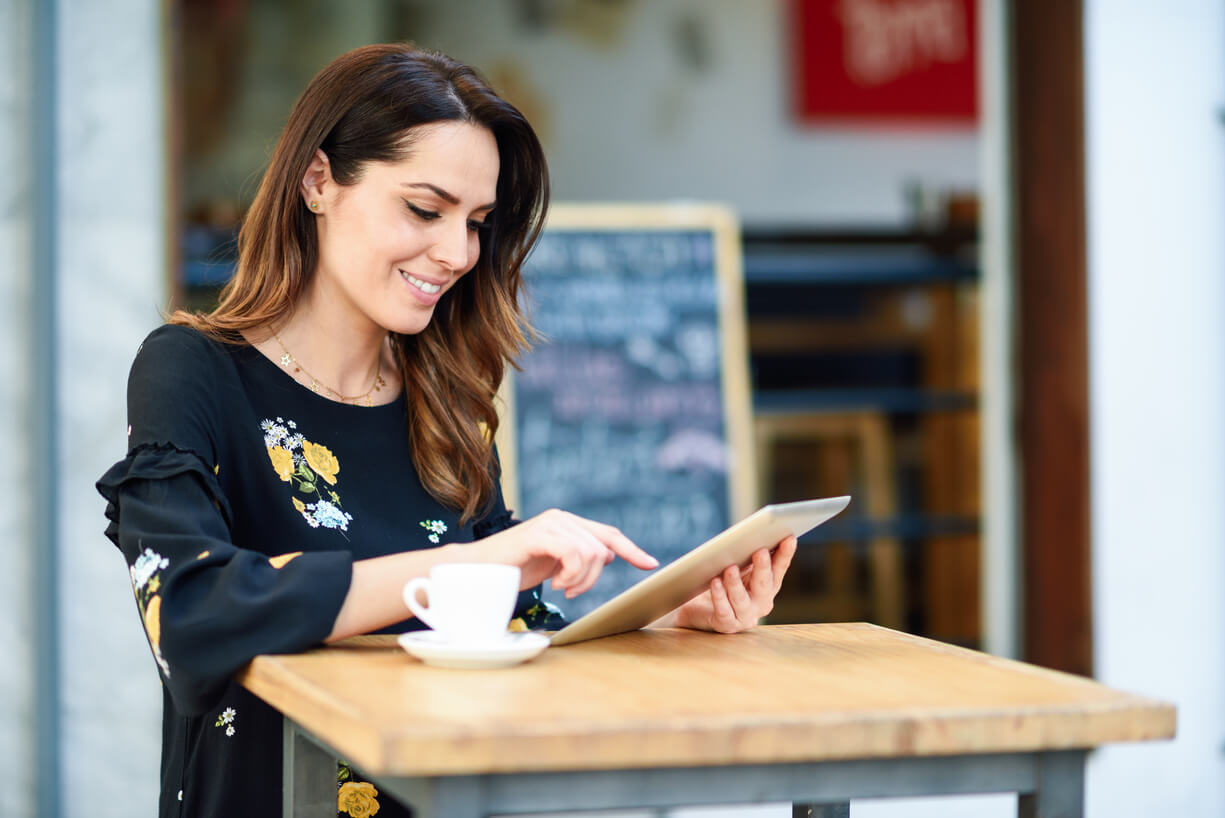 woman having coffee and reading about cbd facts on her tablet